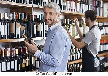 klant, vasthouden, wijn fles, terwijl, verkoper, werkende , in, winkel