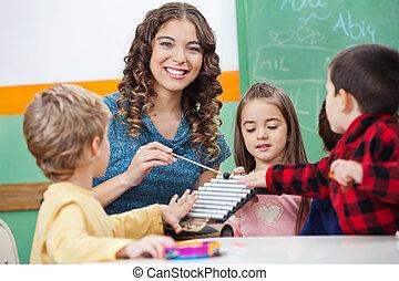 klaslokaal, xylofoon, spelende kinderen, leraar