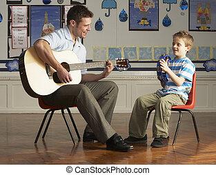 klassrum, spelande gitarr, elev, manlig lärare