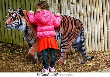 klein meisje, het petting, sumatran tijger