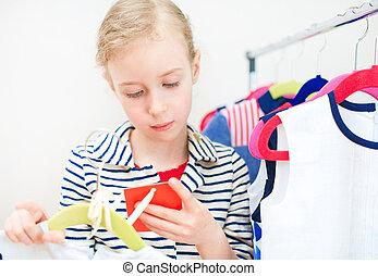 klein meisje, kijken naar, de, prijs, etiket, in, kleding, store.