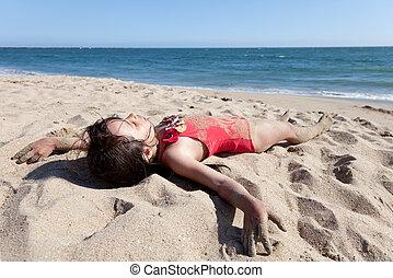 klein meisje, relaxen, op het strand, bedekte in zand