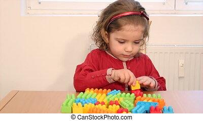 klein meisje, spel met, speelgoed baksteen