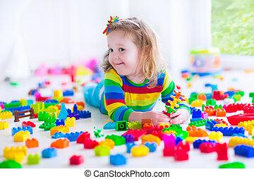 klein meisje, spelend, met, kleurrijke, speelgoed belemmert