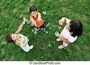 kleine gruppe, von, glücklich, kinder, machen, blasen, und, spielen zusammen, in, natur