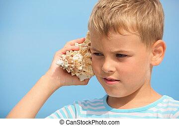 kleiner junge, mit, schale, zuhören, geräusch, von, sea., fokus, auf, links, eye.