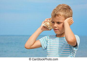 kleiner junge, mit, schale, zuhören, geräusch, von, sea., meer, in, heraus, von, fokus.