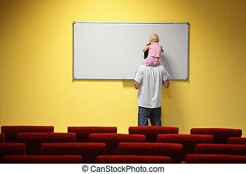 kleines mädchen, gleichfalls, sitzen, auf, father\'s, hals, und, zeichnung, auf, a, board., stuhl, in, heraus, von, fokus.