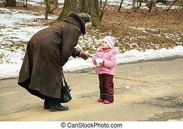kleines mädchen, mit, schneeball, spricht, mit, ältere frau