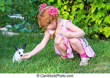 kleines mädchen, petting, a, kaninchen, in, der, gras