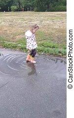 kleines mädchen, sprünge, in, gummistiefel, in, a, puddle.