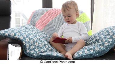 kleinkind, sitzen, stuhl, und, spielende , mit, smartphone