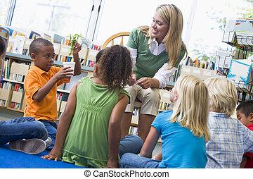 kleuterschool, leraar, en, kinderen, kijken naar, kiemplant, in, bibliotheek