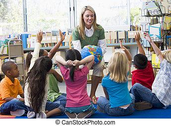 kleuterschool, leraar, en, kinderen, met, hands verheven, in, bibliotheek
