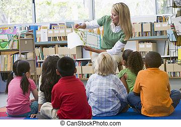 kleuterschool, leraar, lezen aan kinderen, in, bibliotheek