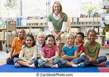 kleuterschool, leraar, zittende , met, kinderen, in, bibliotheek