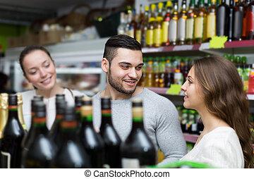 klienci, wybierająca butelka, od, wino, na, napój alkoholowy...