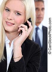 klug, frau, gebrauchend, a, cellphone, als, a, mann, kollege, uhren, in, der, hintergrund