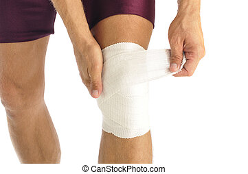 Knee injury - Male athlete wraps knee injury with bandage