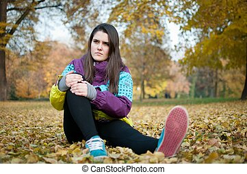 Knee injury - woman sitting in pain
