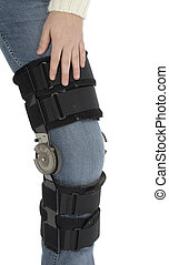 Knee Injury - Woman\\\'s leg wearing knee brace over jeans....
