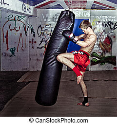Knee kick - Athletic muay thai boxer giving a forceful knee...