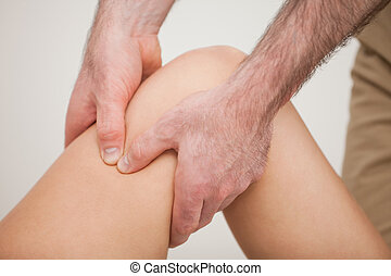 Knee of a patient being held by a physiotherapist