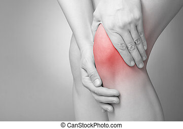 Knee pain - A young woman massaging her painful knee