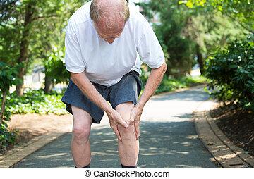Knee pain - Closeup portrait, older man in white shirt, gray...