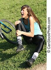 knee pain - Female bike rider takes a tumble, holding her...