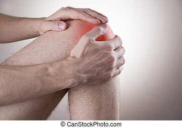 Knee pain in men on gray background