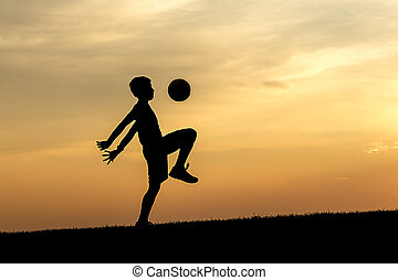 Kneeing the soccer ball at sunset.