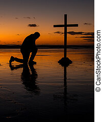 Cross with a man kneel in prayer on a beach at sunset.