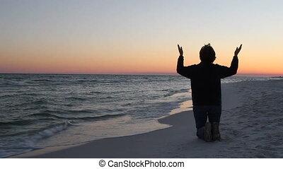 Kneeling In Prayer At Sunset