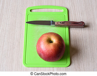 Knife and apple with water drops on a green cutting board.