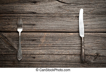 knife and fork on wooden background.