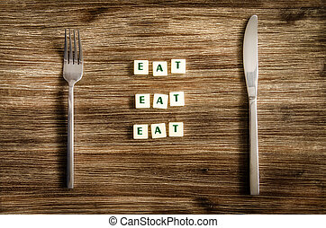 Knife and fork set on wooden table, sign saying Eat - Knife...