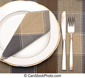 Knife and fork with white plate on wooden table