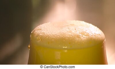 Knife cutting froth from beer. Foam removing from beer glass...
