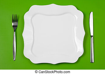 Knife, figured white plate and fork on green background