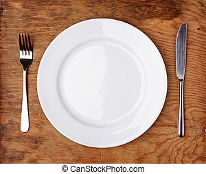 Knife, Fork and plate on wooden table.