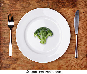 Knife, Fork and plate with broccoli on wooden table.