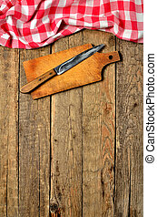 Knife on wooden cutting board and a red checkered tablecloth top frame on wooden table background - vertical photo