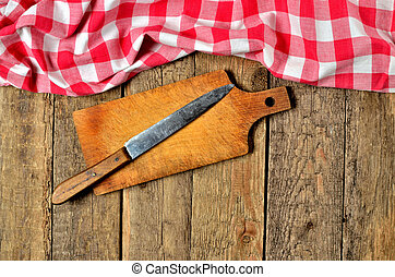Knife on wooden cutting board and a red checkered tablecloth top frame on wooden table background