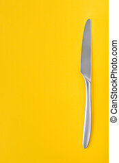 Knife on yellow background, top view.
