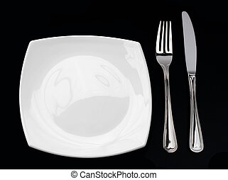 Knife, square white plate and fork on black background