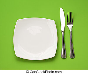 Knife, square white plate and fork on green background