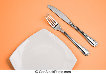Knife, square white plate and fork on pink background