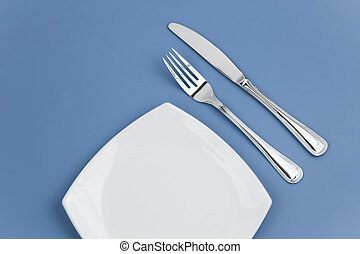 Knife, square white plate and fork on blue background