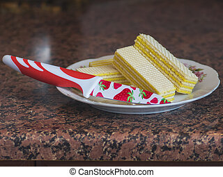 Knife, waffles with lemon on a plate on a table
